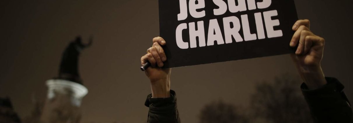 """A man holds a placard which reads """"I am Charlie"""" to pay tribute during a gathering at the Place de la Republique in Paris January 7, 2015, following a shooting by gunmen at the offices of the magazine. Gunmen stormed the Paris offices of the weekly satirical magazine Charlie Hebdo, renowned for lampooning radical Islam, killing at least 12 people, including two police officers in the worst militant attack on French soil in recent decades. The French President headed to the scene of the attack and the government said it was raising France's security level to the highest notch.          REUTERS/Christian Hartmann (FRANCE  - Tags: CRIME LAW MEDIA) - RTR4KFYM"""